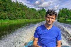 Hombre de mediana edad hermoso que se sienta en el barco severo y que flota a lo largo del río septentrional en fondo hermoso del fotografía de archivo libre de regalías