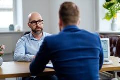 Hombre de mediana edad que asiste a entrevista de trabajo imagen de archivo