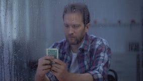 Hombre de mediana edad que cuenta el dinero detrás de la ventana lluviosa, presupuesto pobre, pobreza metrajes