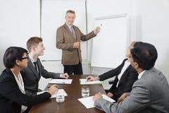 Hombre de mediana edad que usa whiteboard en la reunión de negocios Fotos de archivo