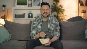 Hombre de mediana edad que ve la TV el comer de las palomitas y el sonreír disfrutando de película en casa metrajes