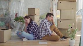 Hombre de mediana edad y mujer de los pares preocupantes que se sientan en el medio de las cajas para moverse almacen de metraje de vídeo
