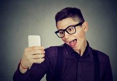 Hombre de mirada divertido que toma a imágenes de él uno mismo con el teléfono elegante Imagen de archivo