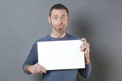 Hombre de mirada pasmado 40s que goza haciendo un anuncio en la exhibición de un parte movible en blanco Foto de archivo