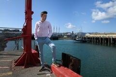 Hombre de moda adulto joven que lleva los pantalones azules y la camiseta clásica que colocan en la pera de la ciudad un pensamie Fotografía de archivo
