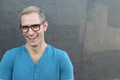 Hombre de moda fresco joven con los vidrios que sonríe y que ríe con el espacio de la copia Imagen de archivo