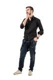 Hombre de moda fresco joven que toca su barba que mira lejos Foto de archivo