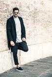 Hombre de moda hermoso, pared de ladrillos blanca Fotografía de archivo libre de regalías
