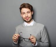 Hombre de moda joven con los vidrios que sonríe, tiro del estudio Foto de archivo libre de regalías