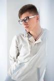 Hombre de moda joven que se inclina en la pared blanca Fotografía de archivo libre de regalías