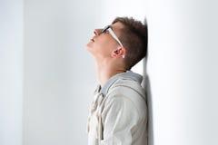 Hombre de moda joven que se inclina en la pared blanca Foto de archivo
