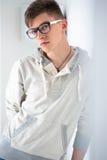 Hombre de moda joven que se inclina en la pared blanca Fotografía de archivo