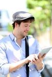 Hombre de moda joven que usa la tableta en las calles Fotografía de archivo libre de regalías