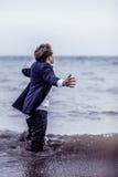 Hombre de moda que se coloca en el mar con los brazos abiertos Imagenes de archivo