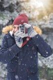 Hombre de moda que toma las fotos con la cámara retra en día nevoso Concepto del viaje de las vacaciones del invierno imagen de archivo libre de regalías