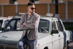 Hombre de moda y elegante alrededor del coche viejo Foto de archivo