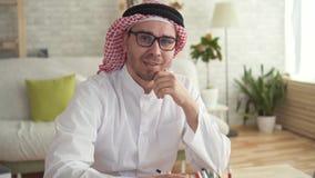 Hombre de negocios árabe del hombre del retrato en el trabajo en un ordenador portátil almacen de video