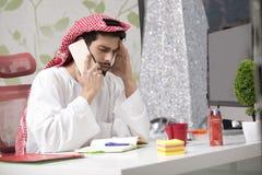 Hombre de negocios árabe joven que habla en el teléfono móvil y finanzas de trabajo sobre coste con el ordenador portátil Fotografía de archivo