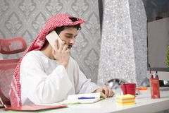 Hombre de negocios árabe joven que habla en el teléfono móvil y finanzas de trabajo sobre coste con el ordenador portátil Imágenes de archivo libres de regalías