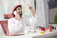 Hombre de negocios árabe joven que habla en el teléfono móvil y finanzas de trabajo sobre coste con el ordenador portátil Imagen de archivo