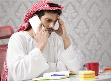 Hombre de negocios árabe joven que habla en el teléfono móvil y finanzas de trabajo sobre coste con el ordenador portátil Imagenes de archivo