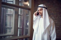 Hombre de negocios árabe que habla en el teléfono celular en compañía imagenes de archivo