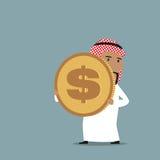 Hombre de negocios árabe que lleva una moneda de oro del dólar Imagenes de archivo