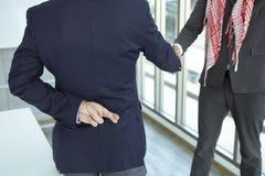 Hombre de negocios árabe que sacude la mano con la muestra de la mentira imagen de archivo