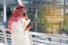 Hombre de negocios árabe usando la tableta y el teléfono móvil Foto de archivo