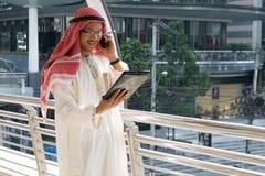 Hombre de negocios árabe usando la tableta y el teléfono móvil Fotos de archivo