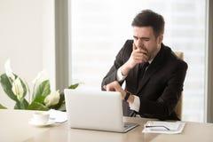 Hombre de negocios aburrido cansado que bosteza en el lugar de trabajo, comprobando tiempo en w Imágenes de archivo libres de regalías
