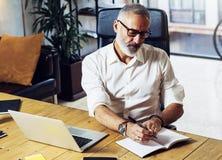 Hombre de negocios acertado adulto que lleva vidrios clásicos y que trabaja en la tabla de madera en estudio coworking moderno st Imagen de archivo libre de regalías