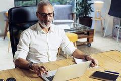 Hombre de negocios acertado adulto que lleva vidrios clásicos y que trabaja en la tabla de madera en estudio coworking moderno st Fotos de archivo libres de regalías