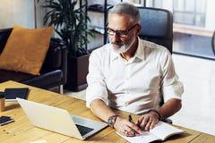 Hombre de negocios acertado adulto que lleva vidrios clásicos y que trabaja en la tabla de madera en estudio coworking moderno st Imagen de archivo