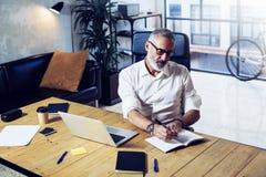 Hombre de negocios acertado adulto que lleva vidrios clásicos y que trabaja en la tabla de madera en estudio coworking moderno st Imágenes de archivo libres de regalías