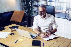 Hombre de negocios acertado adulto que lleva vidrios clásicos y que trabaja en la tabla de madera en oficina coworking moderna st Foto de archivo libre de regalías