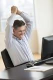 Hombre de negocios acertado With Arms Raised que usa el ordenador Imagenes de archivo