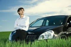 Hombre de negocios acertado con el coche en prado Imágenes de archivo libres de regalías