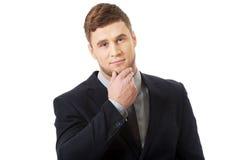 Hombre de negocios acertado con el finger debajo de la barbilla imagen de archivo