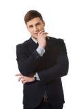 Hombre de negocios acertado con el finger debajo de la barbilla Imagenes de archivo