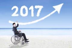 Hombre de negocios acertado con el número 2017 y la flecha Imagen de archivo