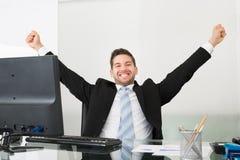 Hombre de negocios acertado con los brazos aumentados en el escritorio Fotografía de archivo libre de regalías