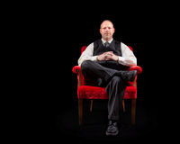 Hombre de negocios acertado en chaleco y lazo que se sienta en silla roja del terciopelo en fondo negro Imagen de archivo libre de regalías
