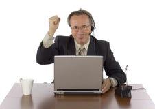 Hombre de negocios acertado en el escritorio con el receptor de cabeza Imagen de archivo libre de regalías