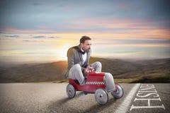 Hombre de negocios acertado en la línea de acabamiento con su coche imagen de archivo libre de regalías