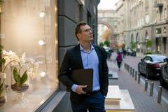 Hombre de negocios acertado en traje con el ordenador portátil en la ciudad fotos de archivo