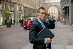 Hombre de negocios acertado en traje con el ordenador portátil en la ciudad imágenes de archivo libres de regalías