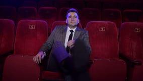 Hombre de negocios acertado en un traje que se sienta solamente en un cine