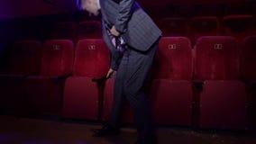 Hombre de negocios acertado en un traje que se sienta solamente en un cine Retrato metrajes