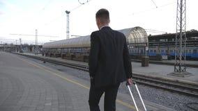 Hombre de negocios acertado irreconocible en traje que camina a través del ferrocarril y que tira de la maleta en las ruedas Cáma almacen de metraje de vídeo